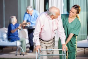 Happy caregiver assisting senior man in home