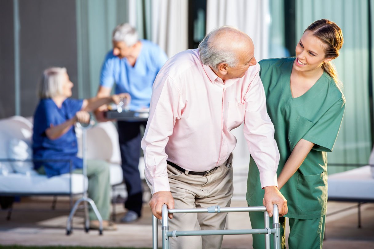 Happy-female-caretaker-assisting-senior-man-in-using-Zimmer-frame-at-nursing-home-yard